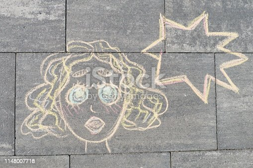 172214590 istock photo Abstract pop art woman face, picture written on gray sidewalk in crayons 1148007718