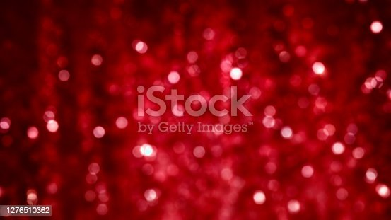Red sparkle glitter tinsel with bokeh effect and selective focus. Festive background with bright gold raining lights. Abstract 3D illustration Christmas and New Year's Eve concept texture template.
