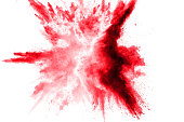 Abstract red dust splattered on white background. Red powder explosion.Freeze motion of red particles splash.