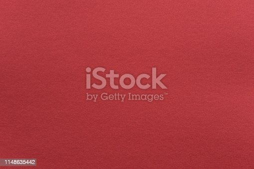 Abstract red glossy paper texture background or backdrop. Empty wrapping paper or shiny paperboard for decorative design element. Grainy surface for Christmas holiday or Chinese new year concept