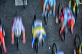 Abstract aerial blurred image of cyclists riding in the pleoton at full speed on an asphalt road.