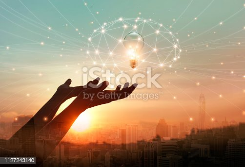 istock Abstract science. Hand holding brain digital network and light bulb inside on networking connection in the city background. Idea and imagination. Creative and inspiration. Innovation technology 1127243140