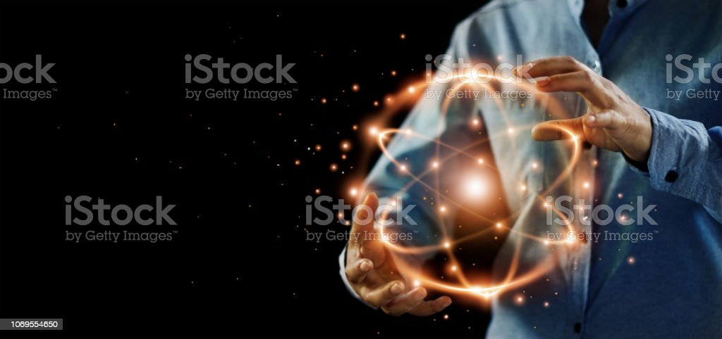 Abstract science, hands holding atomic particle, nuclear energy imagery and network connection on dark background. stock photo