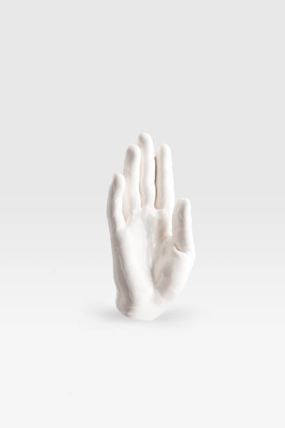 abstract sculpture in shape of human arm in white paint on white surface abstract sculpture in shape of human arm in white paint on white surface sculpture stock pictures, royalty-free photos & images