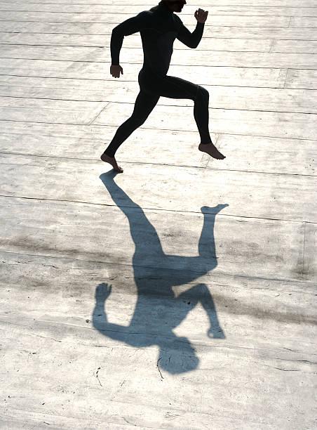 Abstrakte Silhouette sportlichen Mann läuft auf silbernem Hintergrund. – Foto