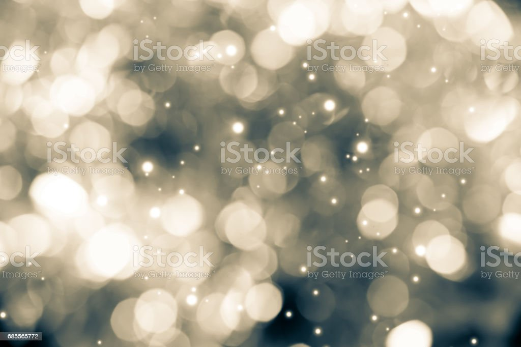 abstract silver glitter blur bokeh background in sepia tone stock photo
