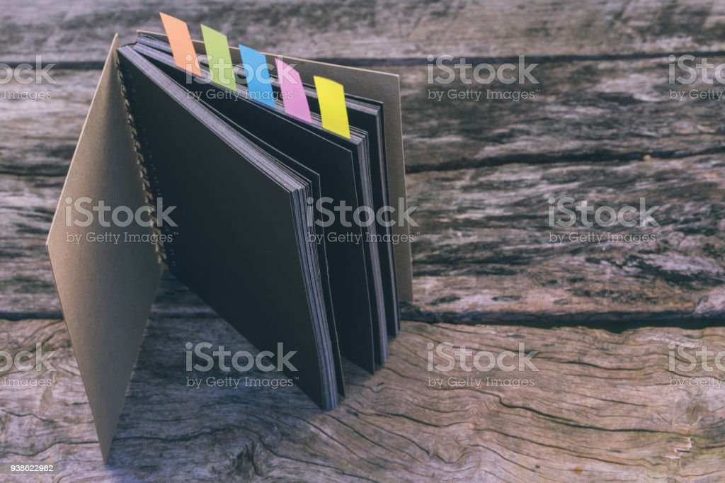 Abstract sketchbook with color note tab. Notebook with colors note tab on wooden table background, Vintage picture tone. Abstract sketchbook with color note tab. Notebook with colors note tab on wooden table background, Vintage picture tone. Archives Stock Photo