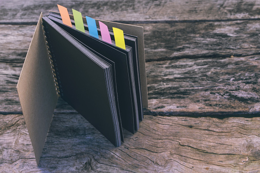 Abstract Sketchbook With Color Note Tab Notebook With Colors Note Tab On Wooden Table Background Vintage Picture Tone Stock Photo - Download Image Now