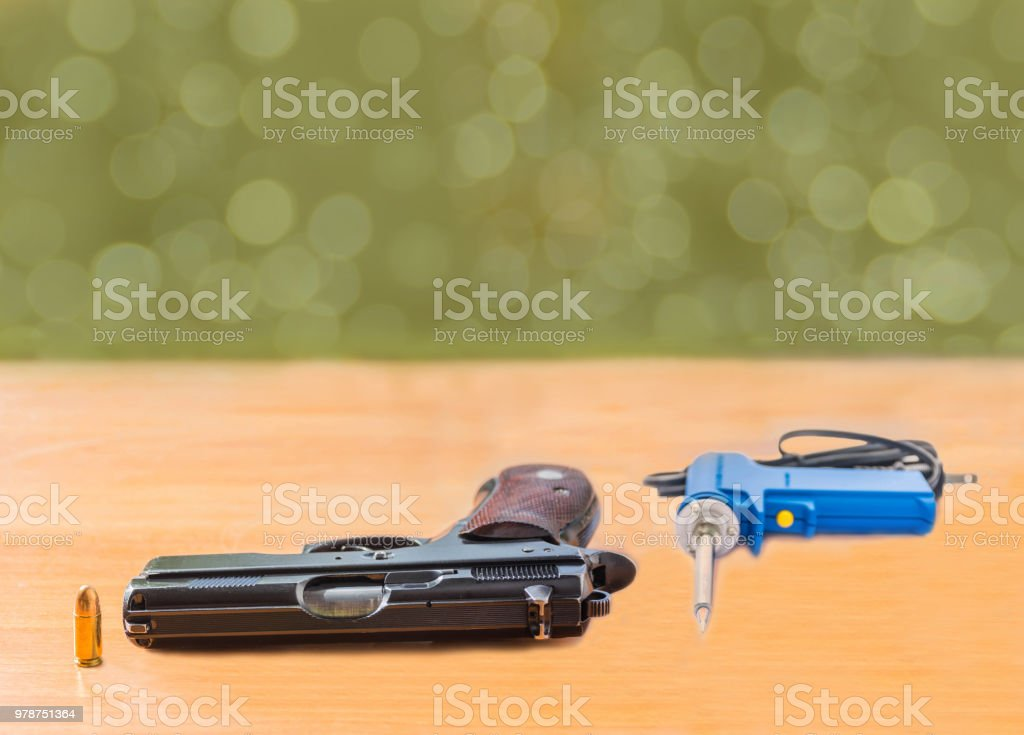 Abstract soft blurred and soft focus the gun, the bullet, the soldering equipment on the blurred old wood with the bokeh background. stock photo