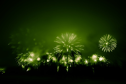Abstract style colorful photo of fireworks in a green tone. Artistic, blurry, colorful look.
