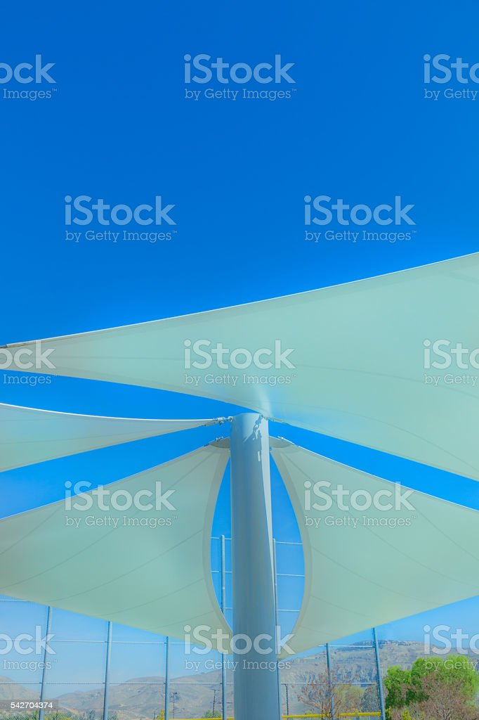 Abstract sun shades against blue sky in sports park (P) stock photo