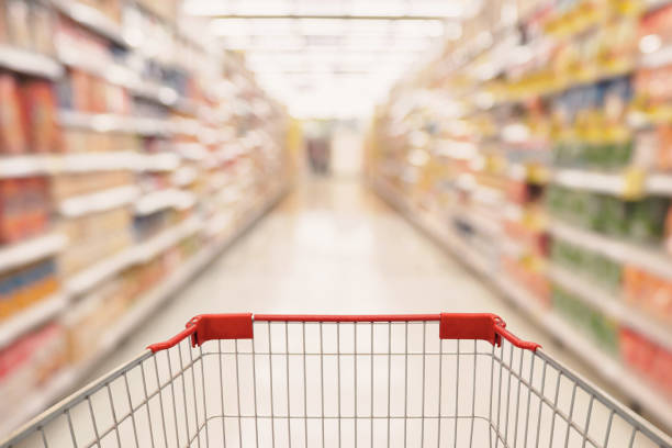 Abstract Supermarket aisle with empty shopping cart stock photo