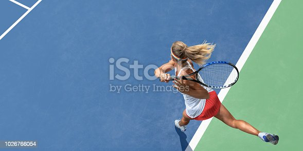 A top view of a professional female tennis player having just served the ball during a tennis match. The athlete wears a white tennis top with red skirt, and is playing on a tennis court with a blue and green hard surface in hot and sunny conditions during the day.