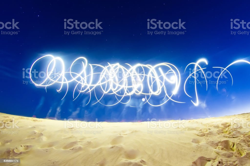 Abstract traces from the light of phone flashlights in the empty on the starry sky stock photo