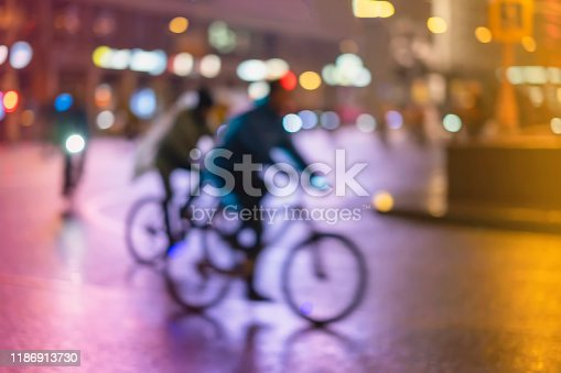 929609038istockphoto Abstract unrecognizable people, riding bikes, night city, illumination bokeh, motion blur. Healthy lifestyle, leisure activity concept. 1186913730