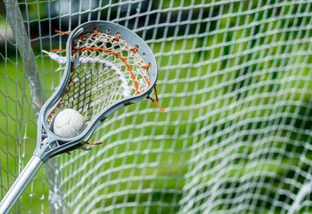 abstract view of a lacrosse stick scooping up a ball - kij do gry w lacrosse zdjęcia i obrazy z banku zdjęć