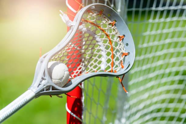 abstract view of a lacrosse stick scooping up a ball. sunny day - kij do gry w lacrosse zdjęcia i obrazy z banku zdjęć