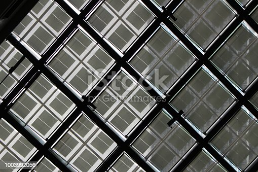 871774704istockphoto Abstract view of geometric glass ceiling 1003992056