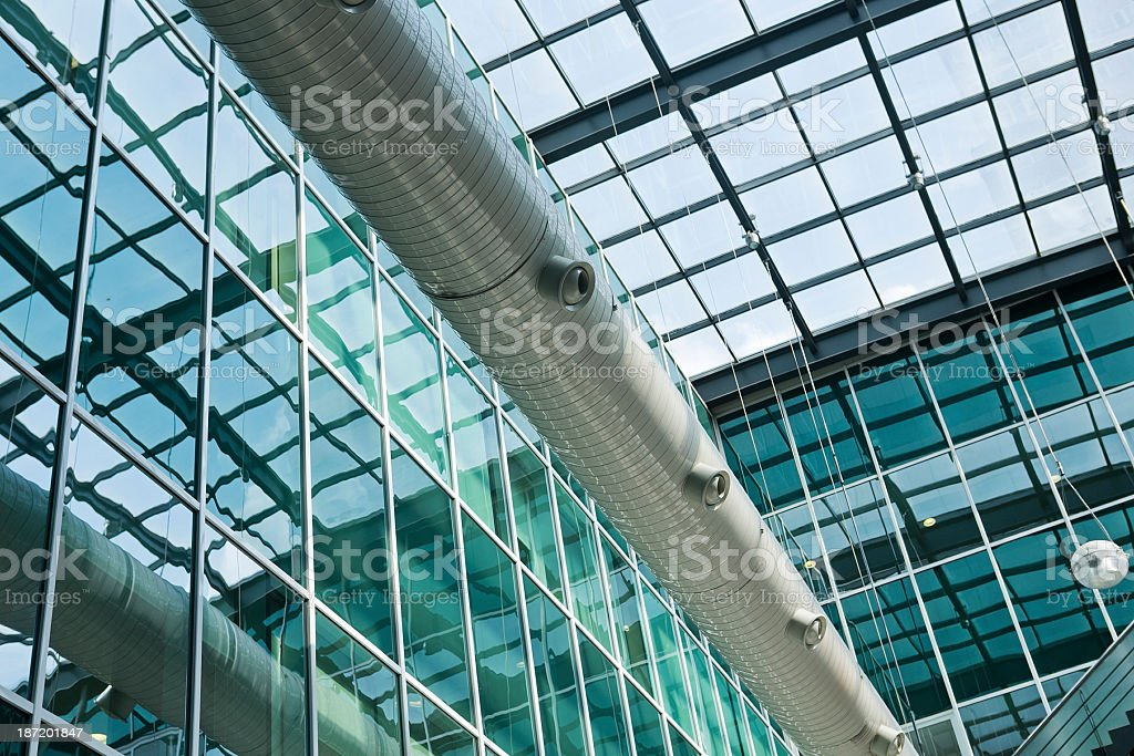 Abstract view of pipe among gridded windows stock photo