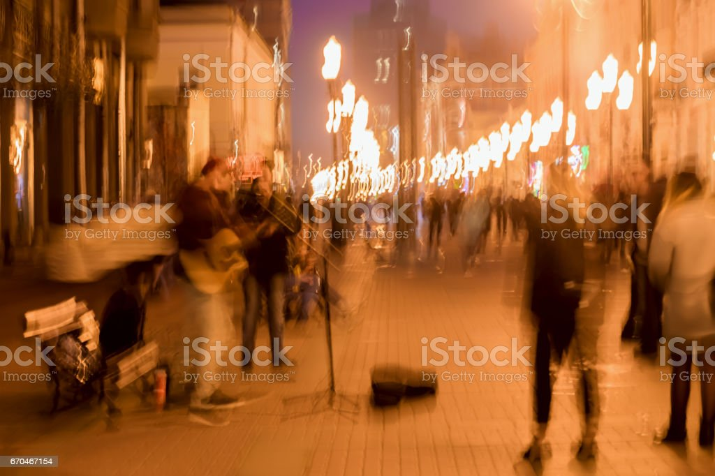 Abstract vintage tone motion, blurred image of street musicians, spectators, bright city lights with bokeh, night urban street life, motion blur for background use stock photo