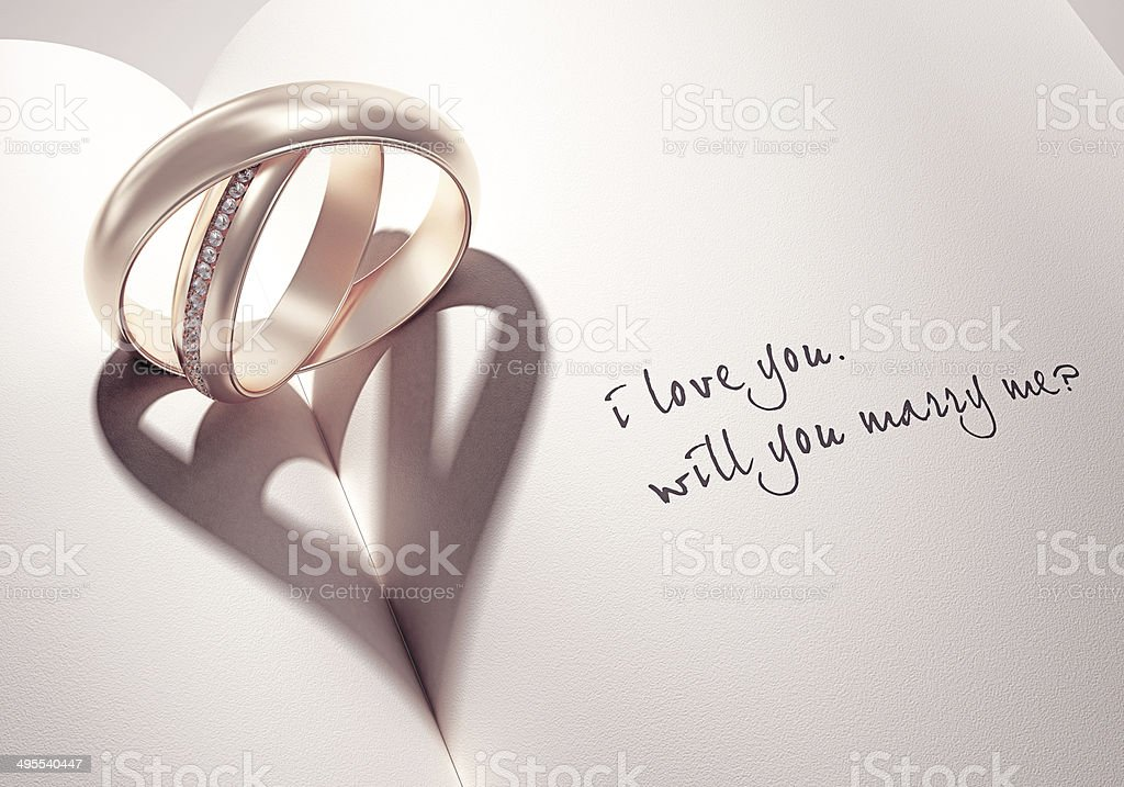 3D abstract wedding rings with heartshadow on a book middle stock photo