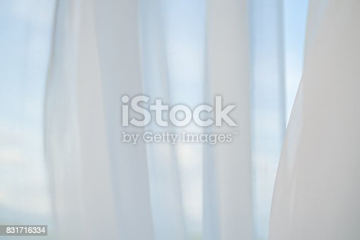 876037346istockphoto Abstract white fabric curtain texture and blue sky background. 831716334