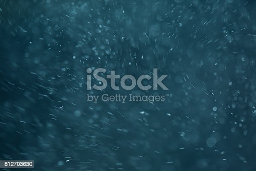 istock abstract White flakes on blue night background 812703630