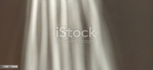 Abstract white gray background. Oblique light rays on a gray background with flickering dots. From left to top, the lines are directed down and to the right.