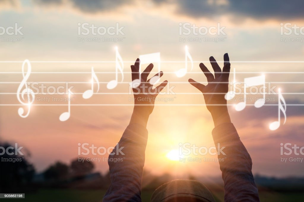 Abstract woman hands touching music notes on nature background, music concept stock photo