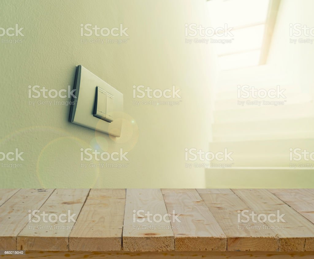 abstract wood table top and lighting switch on wall with lens fare filter stock photo