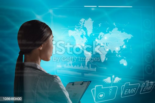 istock Abstract world and global health care technology concept. A woman doctor, or scientist, is contacting research with a futuristic, virtual holographic monitor, that monitors world data. 1056483400