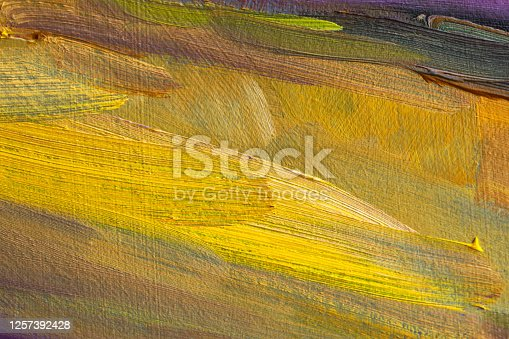 Abstract yellow background with oil paint. Hand-made textured background for signage and banners. A picturesque fragment. Mixing oil paints on canvas.