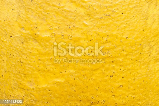 Abstract textured background. Close up view of old yellow paint on a cobblestone from paving stones of Red square in Moscow, Russia.