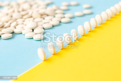 Abstract yellow-blue background,a scattering of pills,pills in a row stand on the edge like dominoes.Bright, conceptual.Healthcare, medicines.Fighting the virus, depression, headache. Calcium