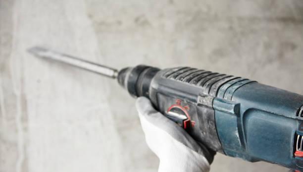 abstractie foto van lawaaierige reparatie. elektrisch gereedschap in de handen van een bouwvakker, geudens tegen een betonnen muur, oude gedragen rock-drill - foto's van hands stockfoto's en -beelden