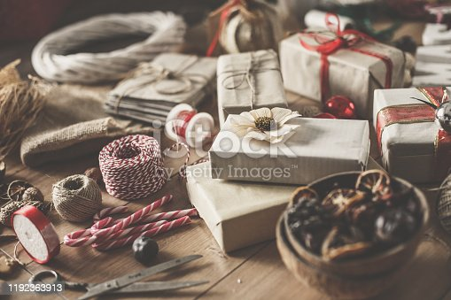 Shot of abundance of rustic looking Christmas presents, candy canes, ribbons, twine and decorations for Christmas arranged on a wooden table.