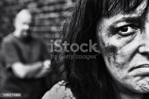 Black-and-white shot of female victim of domestic abuse with her battering partner standing behind her looking threatening.