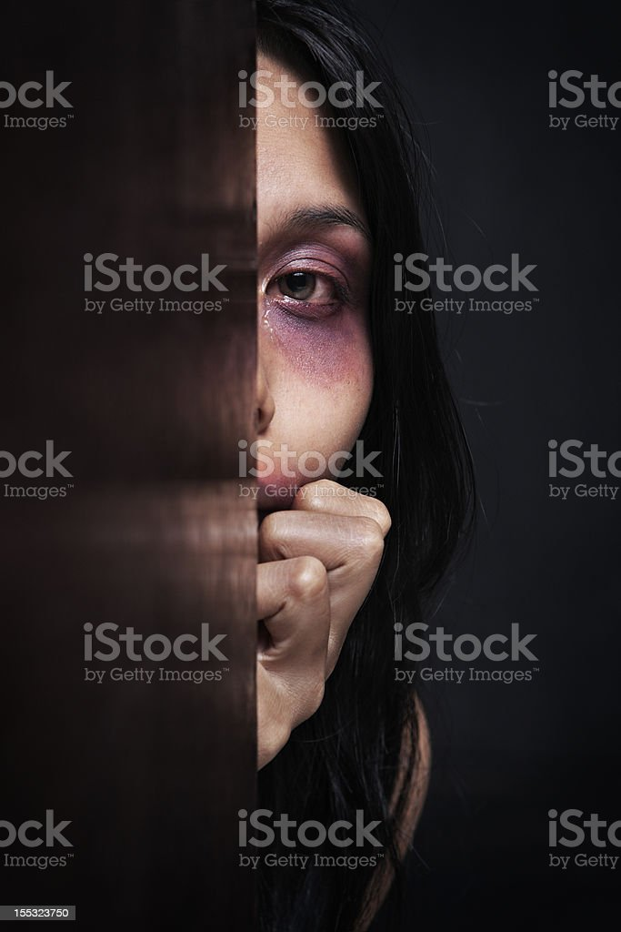 Abused woman hiding in dark stock photo