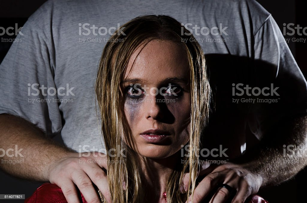 abused woman with man standing behind her horizontal stock photo