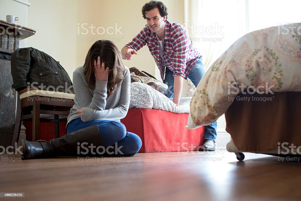 Abusive Relationship A man can be seen yelling at a young woman who is holding her head in her hands. They are in a dingy bedsit and he appears very aggressive. 2015 Stock Photo