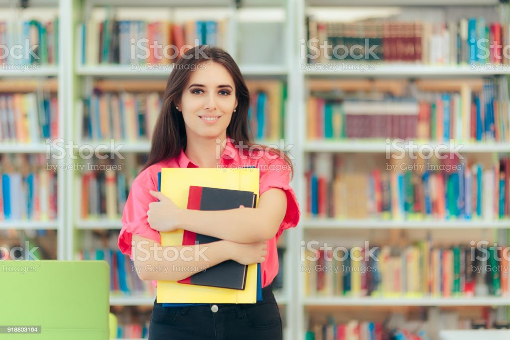 Academic Girl Holding her Book and Papers in a Library stock photo