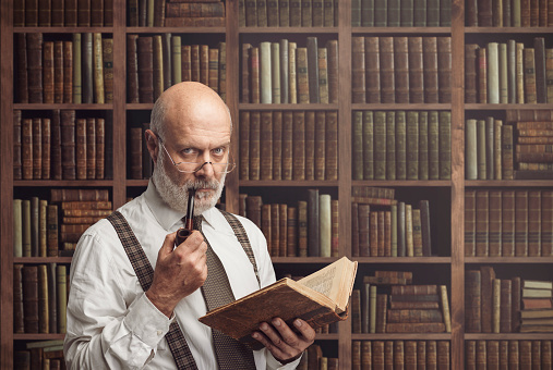 Senior academic professor reading an old book in the library, knowledge, learning and education concept