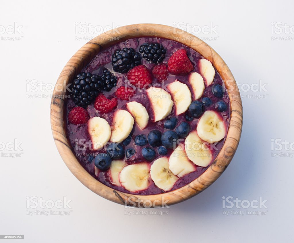 acai berry smoothie bowl in a wooden bowl on white background stock photo