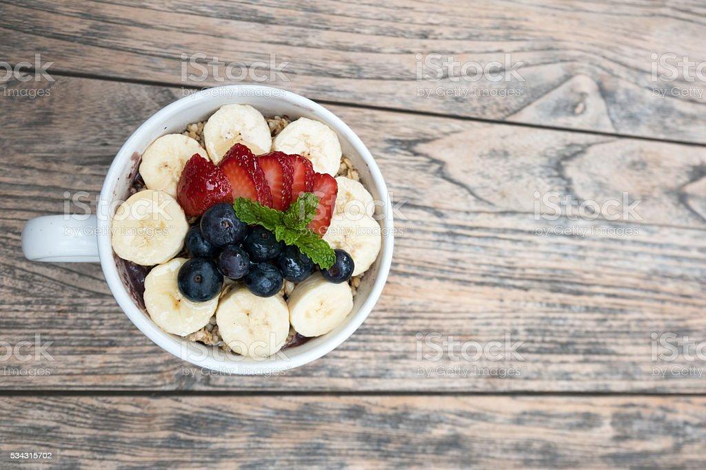 Acai bowl with strawberry, blueberry, banana, granola on wooden table. stock photo