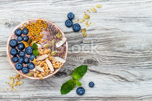 Acai breakfast superfoods smoothies bowl topped with chia, flax and pumpkin seeds, bee pollen, granola, coconut flakes and blueberries. Overhead, top view, flat lay