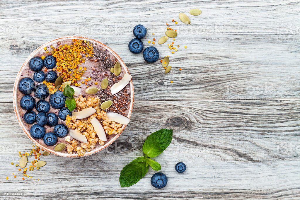 Acai breakfast superfoods smoothies bowl with chia seeds, bee pollen stock photo