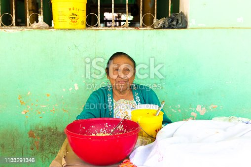 Acanceh, Yucatan, Mexico: A beautiful senior female vendor sits smiling against a green wall in a farmers market selling food in Acanceh, a Maya village about 20 kilometers from Merida in the Yucatan Peninsula.