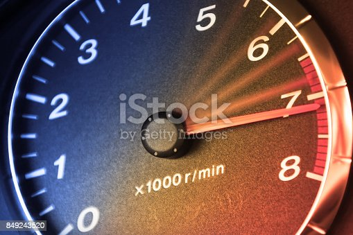 Arrow of tachometre in red zone. Car dashboard. Accelerating.