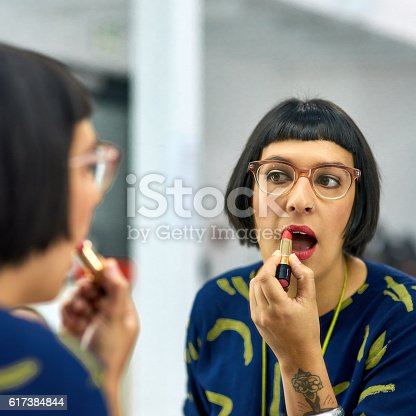 istock Accentuating her lips with a little color 617384844