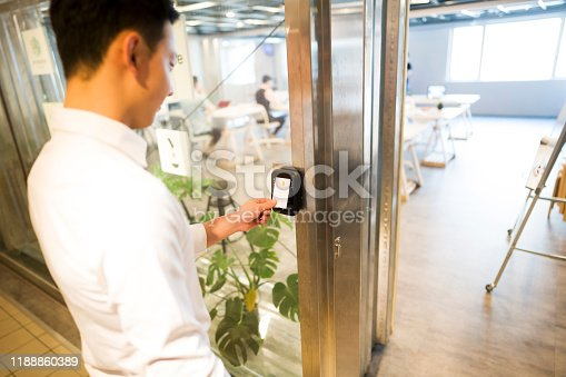 Young taiwanese man unlocking door at his office with an electronic key card